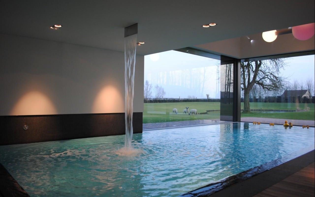 Prachtig wit zwembad met houten plage rondom bob monteyne for Binnen zwembaden